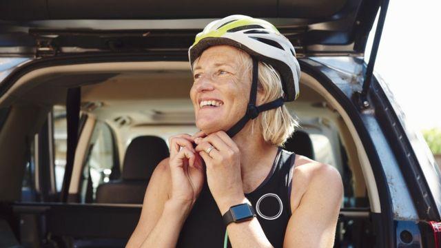 Una mujer colocándose un casco de ciclista.