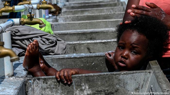 Una madre baña a su hija pequeña en un centro de acogida de migrantes en Panamá.